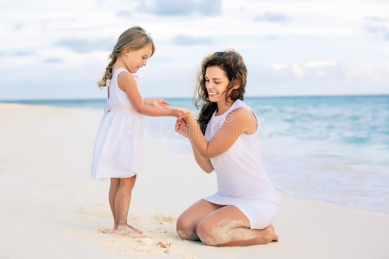 使用在马尔代夫的海滩的母亲和小女儿在暑假 库存照片