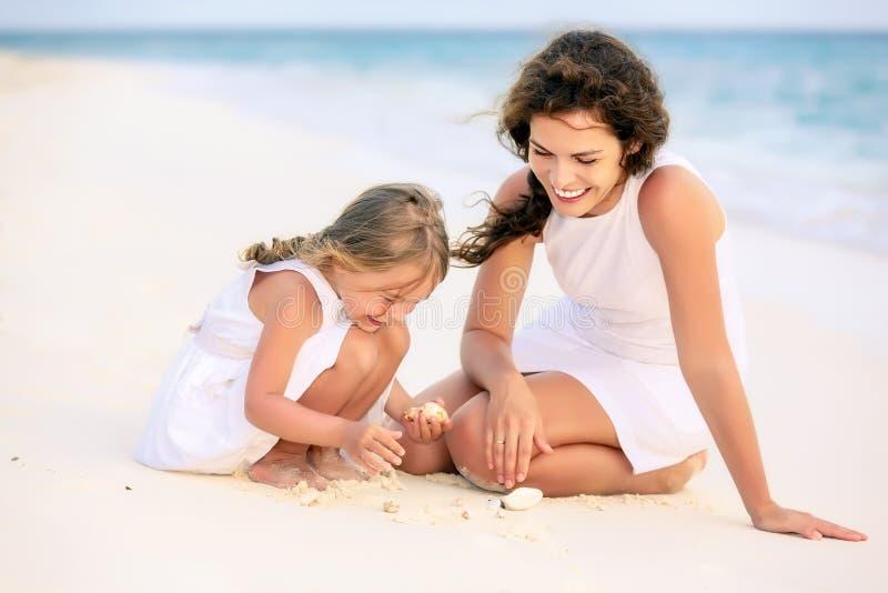 使用在马尔代夫的海滩的母亲和小女儿在暑假 免版税库存照片
