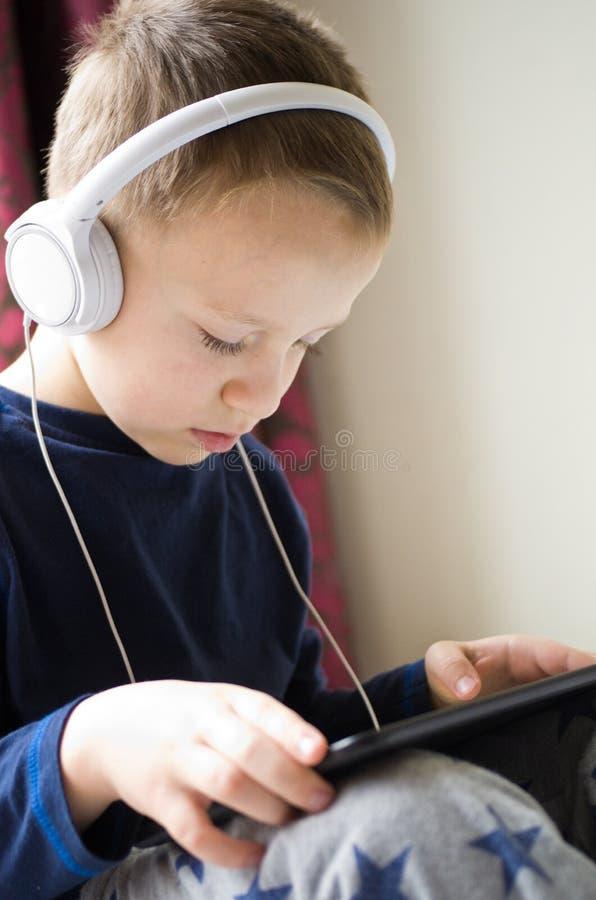 使用在他的手机的年轻男孩在床上 免版税库存图片