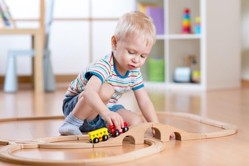 使用在他的有玩具火车的屋子里的儿童男孩 免版税库存照片