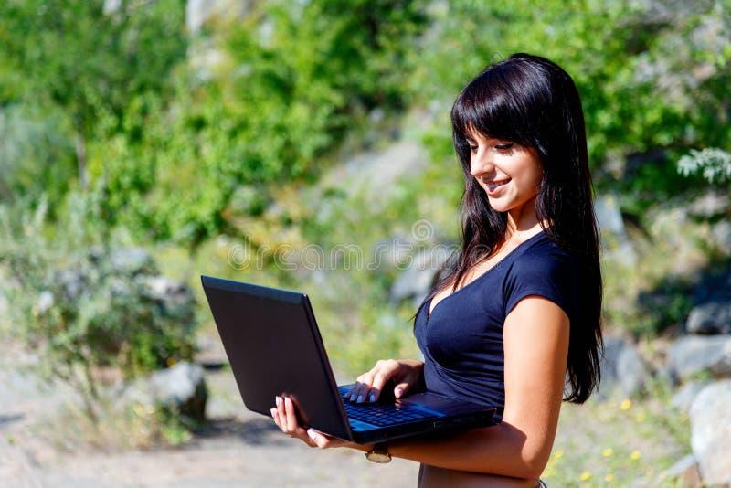使用在绿草背景的微笑的深色的女孩膝上型计算机 库存图片