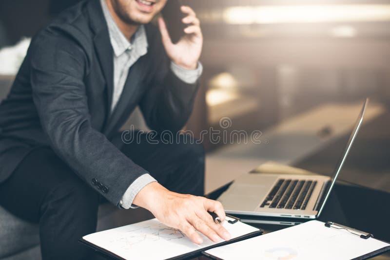 使用在r的巧妙的电话在衣服的英俊的商人和镜片说在电话里在办公室,侧视图射击了人` s手 免版税库存图片