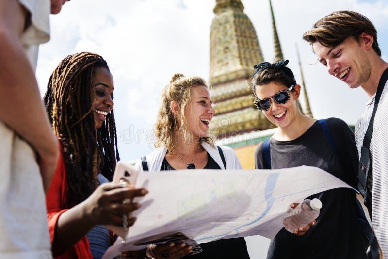 使用地图的小组游人在泰国寺庙 免版税库存照片