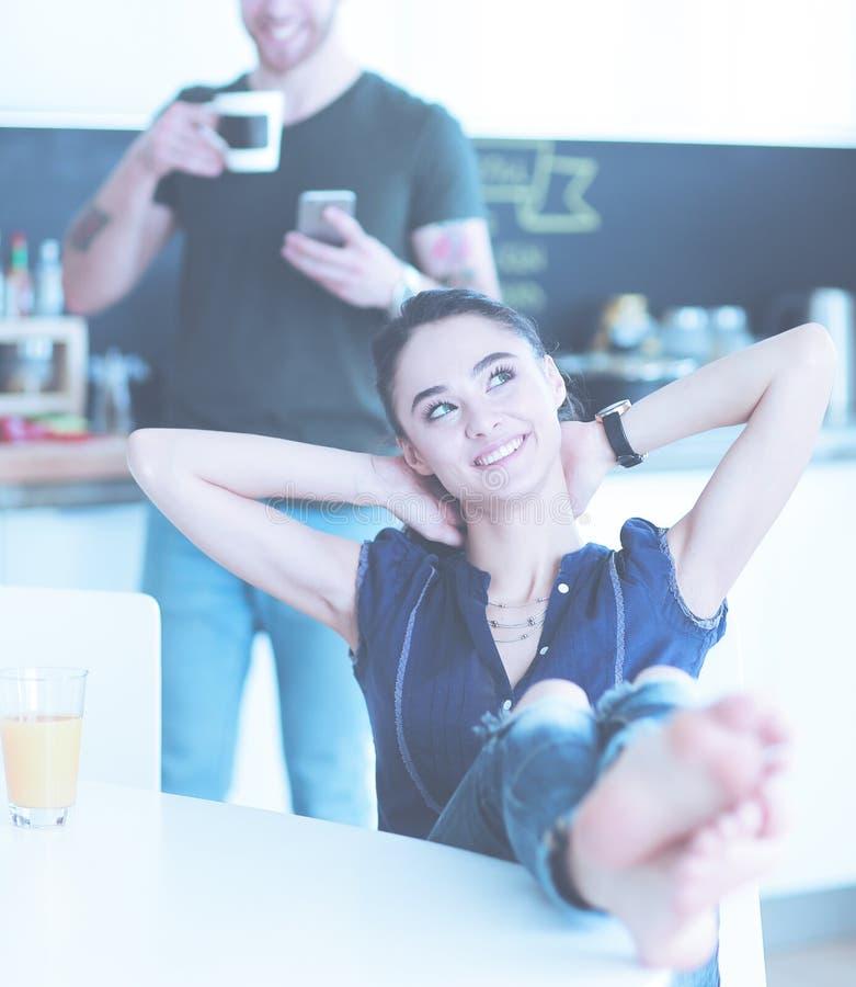 使用坐在厨房里的智能手机的愉快的夫妇 免版税图库摄影