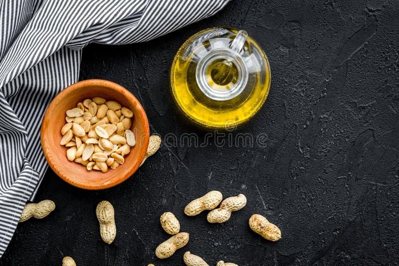 使用坚果油作为化妆用品 在瓶子的花生油在碗的花生附近在黑背景顶视图拷贝空间 图库摄影
