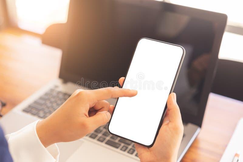 使用垂直的白色屏幕智能手机大模型的妇女手 图库摄影