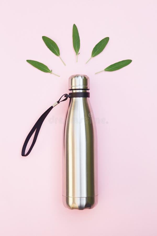 使用塑料bo,金属在桃红色背景和绿色叶子隔绝的水瓶,顶视图,去绿色,环境保护,停止 库存图片