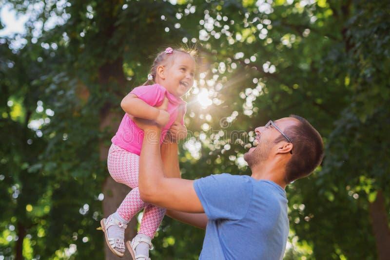 使用外面在公园的父亲和女儿 免版税库存照片