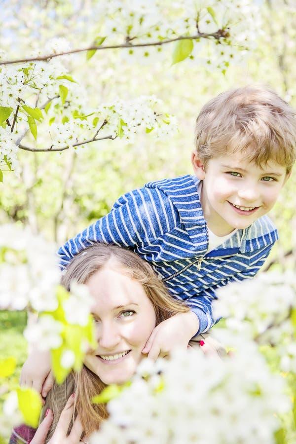 使用外面在春天的笑的母亲和孩子 免版税库存图片