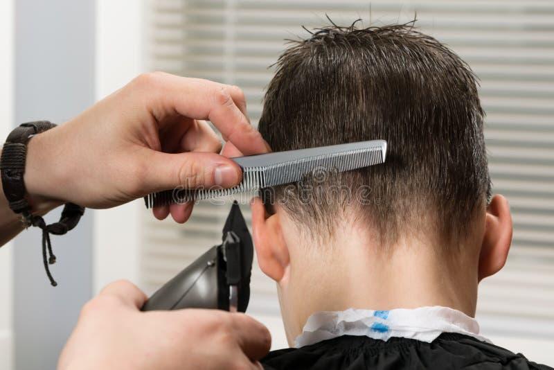 使用头发剪刀和梳子,剪头发给男孩在头背面 免版税库存图片