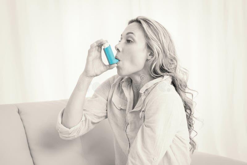 使用她的在长沙发的金发碧眼的女人哮喘吸入器 免版税图库摄影