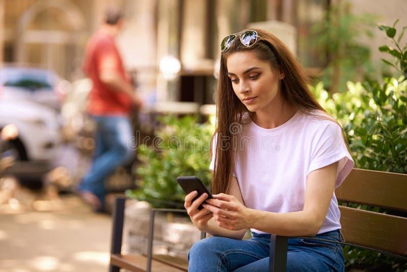 使用她的手机和正文消息的美丽的年轻女人,当坐在街道上时的长凳 库存照片