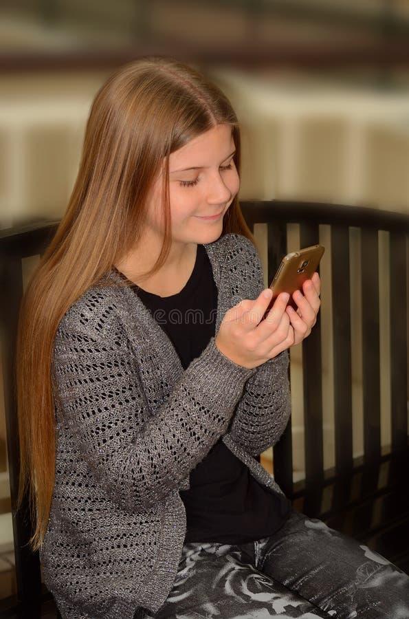 使用她的手机的俏丽的女孩 免版税库存照片