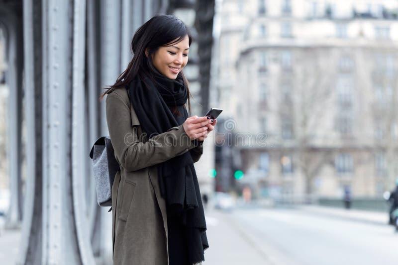 使用她的手机的微笑的亚裔少妇在街道 库存图片