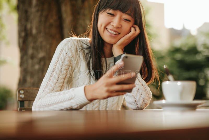 使用她的手机的愉快的少妇在咖啡馆 免版税图库摄影