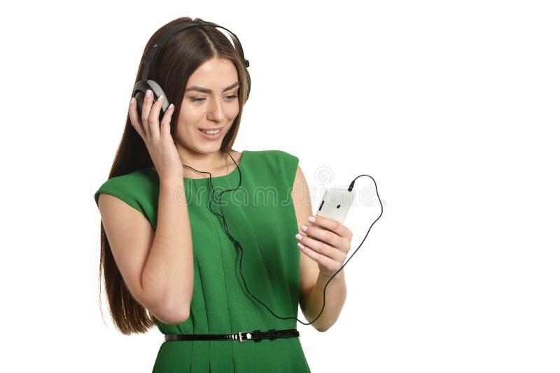 使用她的手机的愉快的美丽的女孩听到音乐w 免版税图库摄影