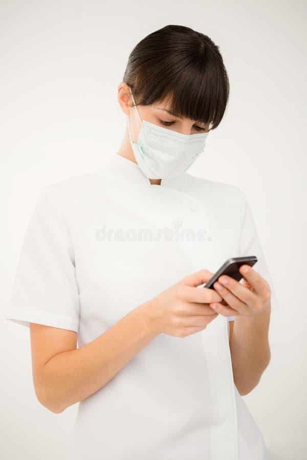 使用她的手机的护士的画象 免版税库存照片