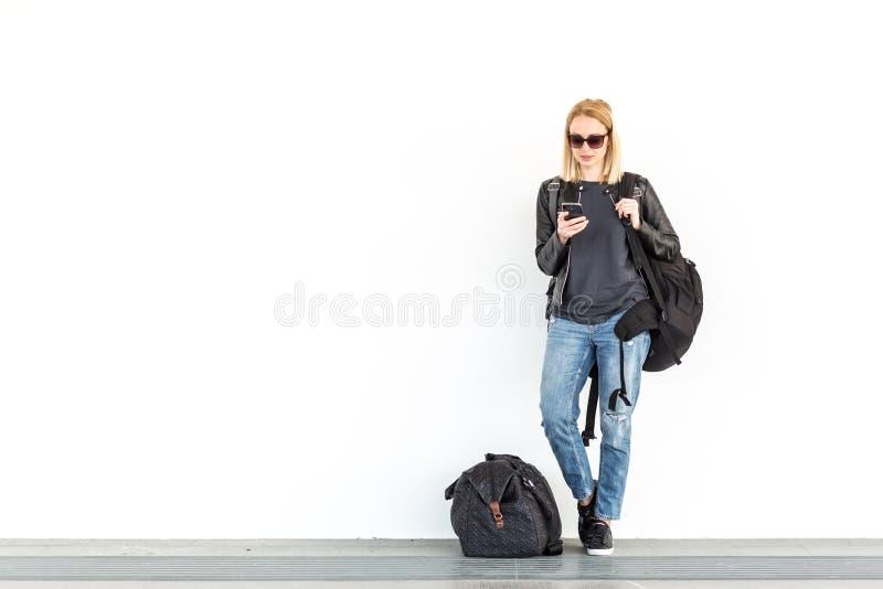 使用她的手机的时兴的少妇,当站立和等待对在驻地丝毫时的简单的白色墙壁 免版税库存图片