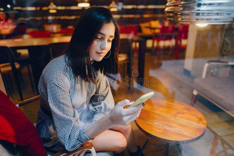 使用她的手机的深色的女孩到达朋友 免版税库存照片