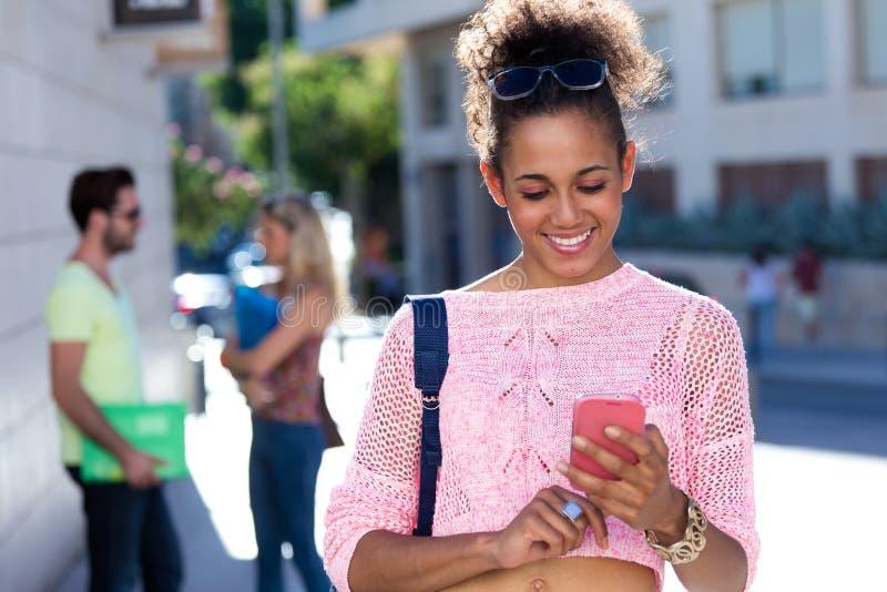 使用她的手机的美丽的学生女孩在街道 免版税库存图片