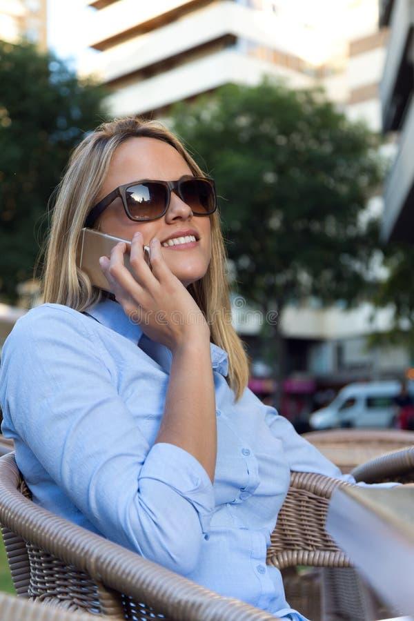 使用她的手机的美丽的少妇在餐馆ter 免版税库存照片