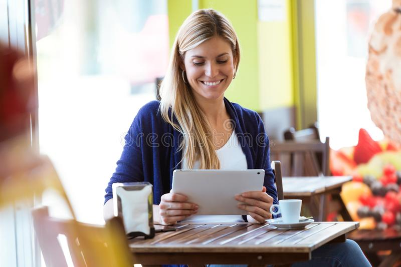 使用她的数字式片剂的美丽的少妇在咖啡店 库存照片