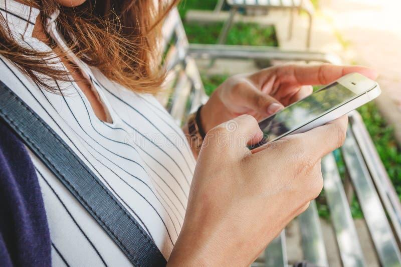 使用她的智能手机的少妇手观看的媒介的,坐一条长凳在公园 在线购物概念 库存照片