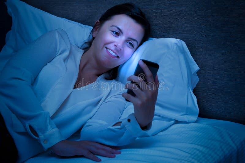 使用她的智能手机的快乐的妇女 库存图片