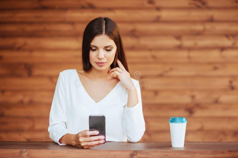 使用她的智能手机的美丽的少妇和喝咖啡 免版税库存照片