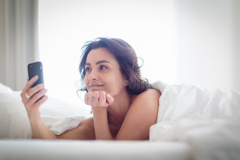 使用她的智能手机的美丽的年轻女人在床 免版税库存图片