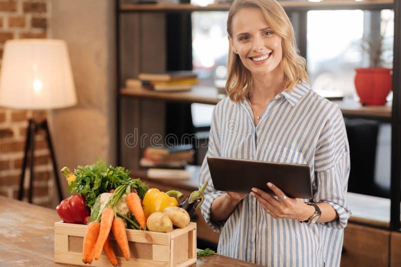 使用她的片剂的活跃精明的夫人在厨房 免版税库存图片