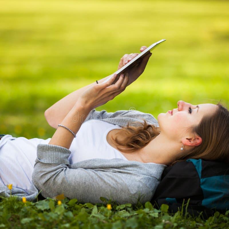 使用她的片剂计算机的少妇,当放松户外时 库存图片