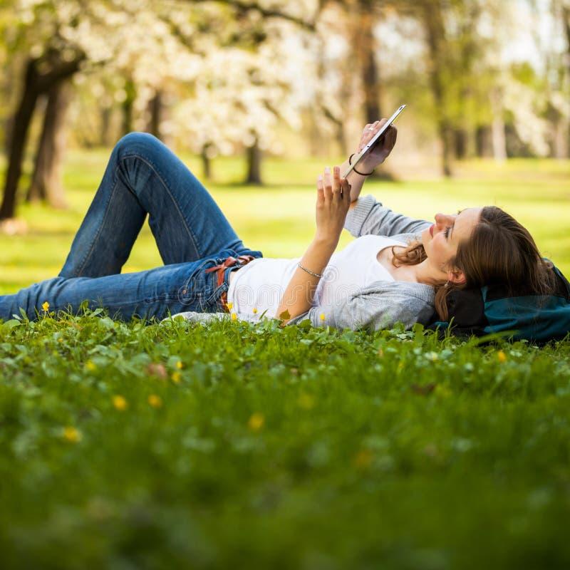 使用她的片剂计算机的少妇,当放松户外时 免版税库存图片