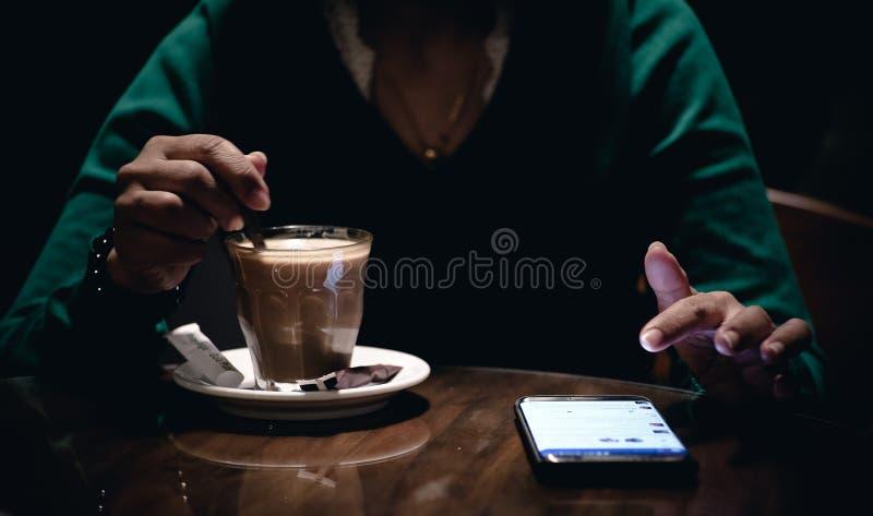 使用她的电话和饮用的咖啡的一名成年女性在一个暗室 库存图片