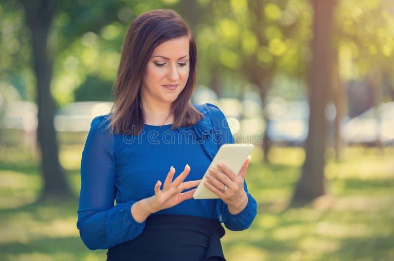 使用她的电话的快乐的年轻女人 免版税库存图片