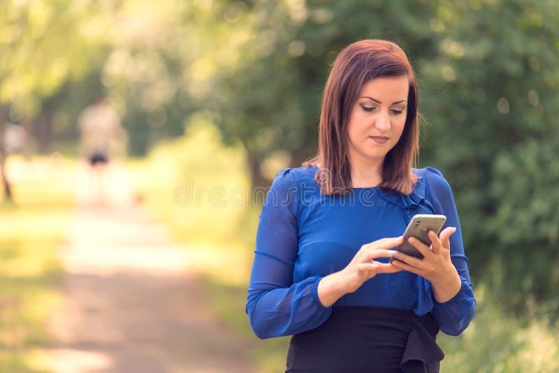 使用她的电话的快乐的年轻女人 免版税库存照片