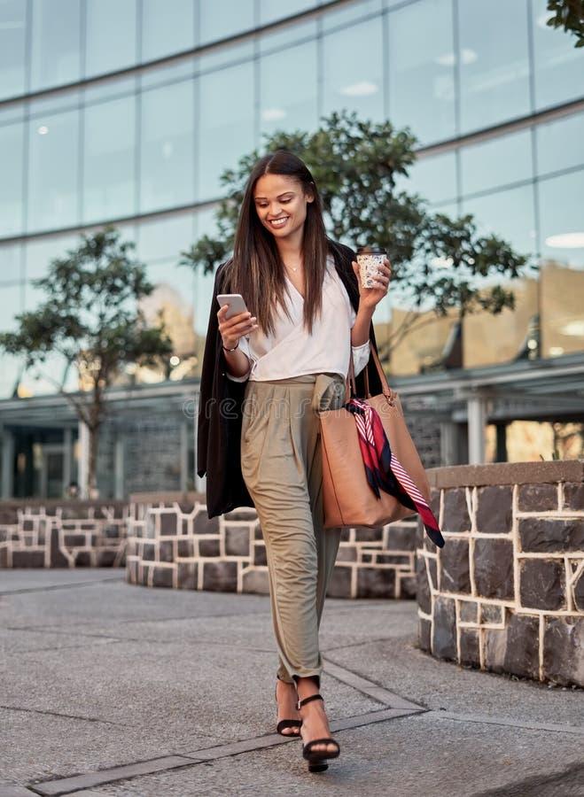 使用她的电话的时髦的年轻女人,当走在城市街道上时 免版税图库摄影
