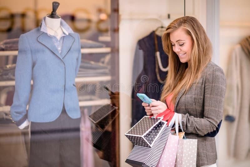 使用她的电话的美丽的妇女,当窗口购物时 库存照片
