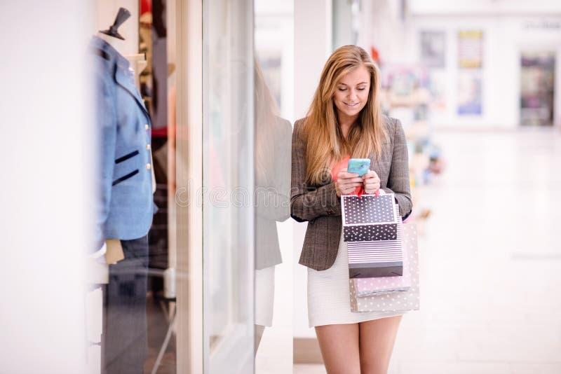 使用她的电话的美丽的妇女,当窗口购物时 图库摄影