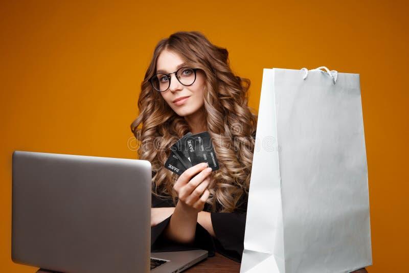 使用她的膝上型计算机和信用卡为网络购物,拿着黑卡片的一件黑礼服的好妇女的逗人喜爱的微笑的女孩 免版税库存照片