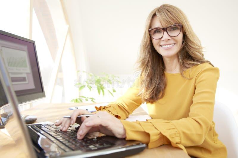 使用她的膝上型计算机的可爱的女实业家在办公室 免版税图库摄影