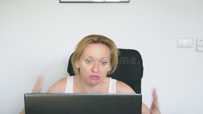 使用她的膝上型计算机的妇女,坐在桌,恼怒和激怒,发誓 人力的情感 互联网瘾概念 库存照片