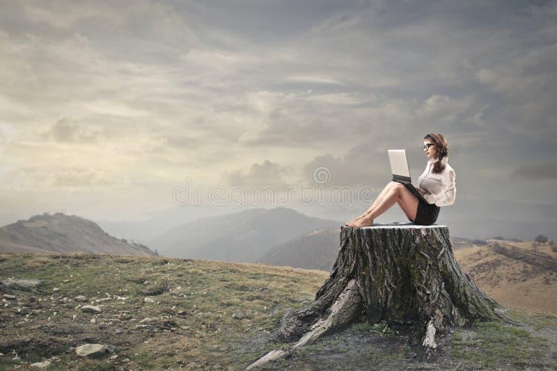 使用她的膝上型计算机的少妇 免版税库存照片