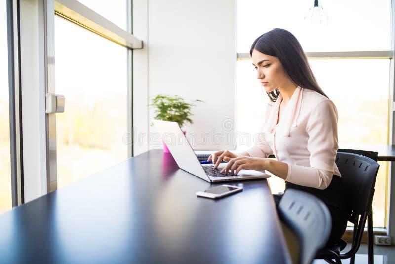 使用她的膝上型计算机的年轻美丽的妇女,当坐在椅子在她的工作地点时 免版税库存照片