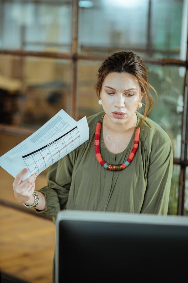 使用她的资料的深色头发的女实业家,当吹一些空气时 免版税库存图片