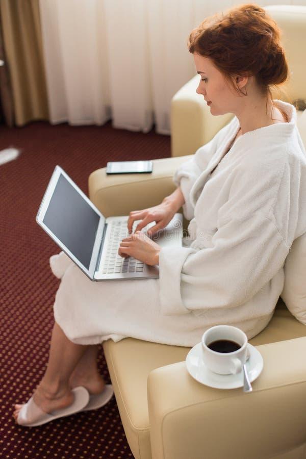 使用妇女年轻人的旅馆膝上型计算机 库存图片