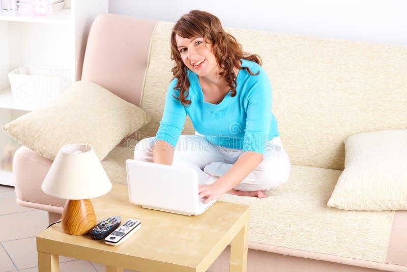 使用妇女年轻人的膝上型计算机坐的&# 库存照片