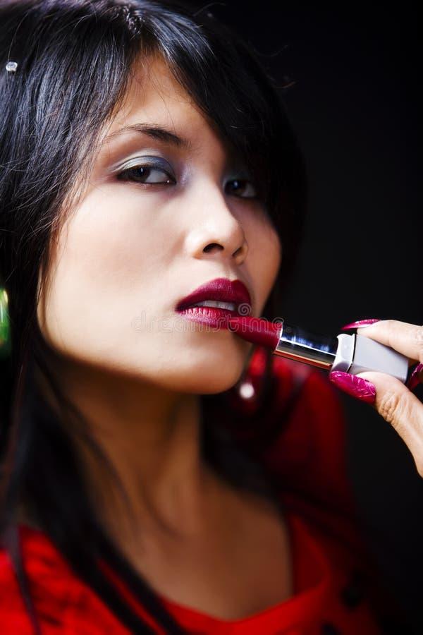 使用妇女年轻人的lisptick 图库摄影