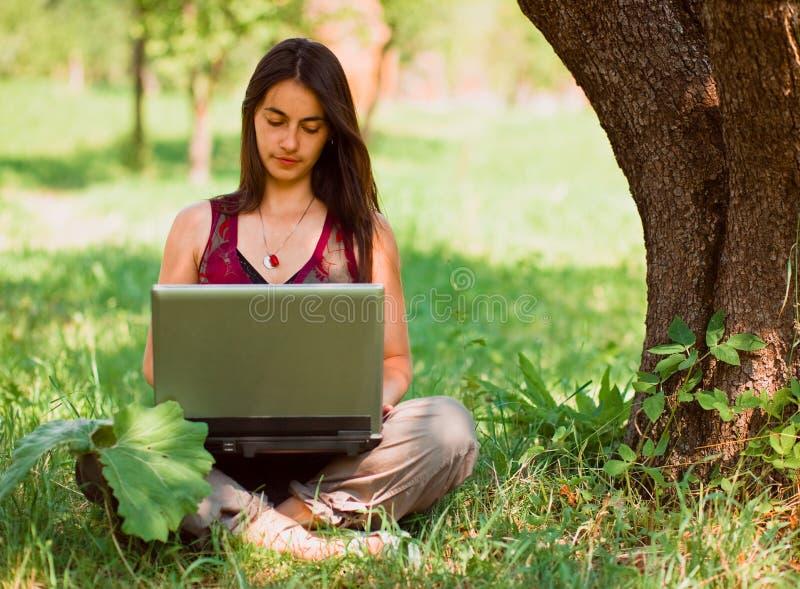 使用妇女年轻人,户外她的膝上型计& 库存照片