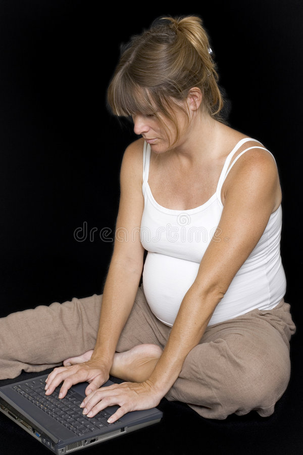 使用妇女的下来膝上型计算机怀孕的开会 免版税库存照片